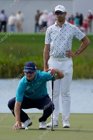 Zach Johnson and Cameron Tringale look at their shots on the 17th hole during the third round of the Honda Classic golf tournament, in Palm Beach Gardens, Fla