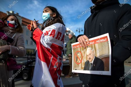 Stock Photo of Demonstrator holds a picture of Belarusian President Alexander Lukashenko with the inscription ''we are not slaves'' during a protest demanding freedom for political prisoners in Belarus at the Cathedral Square in Vilnius, Lithuania