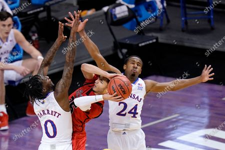 Eastern Washington guard Michael Meadows, center, gets pressure from Kansas guard Marcus Garrett (0) and teammate Bryce Thompson (24) during the first half of a first-round game in the NCAA college basketball tournament at Farmers Coliseum in Indianapolis