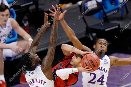 Eastern Washington guard Michael Meadows, center, gets pressure from Kansas guard Marcus Garrett (0) and teammate Bryce Thompson (24) while attempting to shoot during the first half of a first-round game in the NCAA college basketball tournament at Farmers Coliseum in Indianapolis