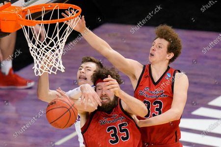 Kansas guard Christian Braun, left, battles Eastern Washington forward Tanner Groves (35) and teammate Jacob Groves (33) for a rebound during the second half of a first-round game in the NCAA college basketball tournament at Farmers Coliseum in Indianapolis