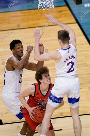 Eastern Washington guard Jacob Groves (33) is pressured by Kansas forward David McCormack, left, and teammate Christian Braun (2) as he get up for a shot during the second half of a first-round game in the NCAA college basketball tournament at Farmers Coliseum in Indianapolis