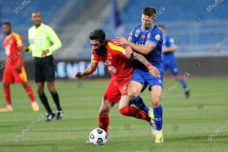 Al-Hilal's player Luciano Vietto (R) in action against Al-Qadisiyah's Rhys Williams (L) during the Saudi Professional League soccer match between Al-Hilal and Al-Qadisiyah at Prince Faisal Bin Fahd Stadium, in Riyadh, Saudi Arabia, 20 March 2021.