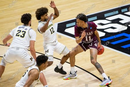 Texas Southern's Jordan Gilliam (11) dribbles behind his back to move around Michigan's Mike Smith (12) and Michigan's Brandon Johns Jr. (23) during the second half of a first-round game in the NCAA men's college basketball tournament, at Mackey Arena in West Lafayette, Ind