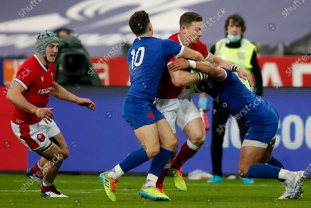 Wales' George North, center, is tackled during the Six Nations rugby union international between France and Wales at the Stade de France in Saint-Denis, near Paris