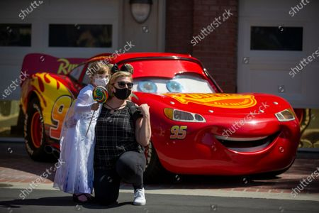 """Rachel C., 6, and her mom, Lauren C., of Prescott, AZ, pose for photos with Lightning McQueen from the Cars movie during the debut of Disney California Adventure's """"A Touch of Disney"""" food event at Disney California Adventure Park Thursday, March 18, 2021 in Anaheim, CA. This spans the entire DCA park and allows guests to eat, interact with characters and explore the grounds. A Touch of Disney, the new limited-time ticketed experience at Disney California Adventure Park which has sold out, takes place March 18 through April 19, 2021. (Allen J. Schaben / Los Angeles Times)"""
