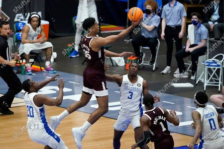 Saint Louis guard Fred Thatch Jr. (20), Javonte Perkins (3), and Jordan Goodwin (0) defend as Mississippi State forward Tolu Smith (35) leaps to the basket for a shot during the first half of an NCAA college basketball game in the first round of the NIT Tournament, in Frisco, Texas