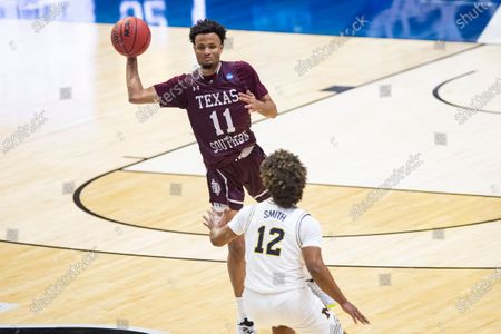 Texas Southern's Jordan Gilliam (11) passes over Michigan's Mike Smith (12) during a first round game in the NCAA men's college basketball tournament, at Mackey Arena in West Lafayette, Ind. Michigan won 82-66