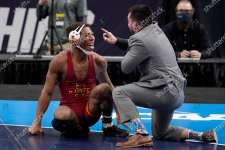 Stock Picture of Iowa State's David Carr celebrates with coach Brent Metcalf, right, after defeating Rider's Jesse Dellavecchia during their 157-pound match in the finals of the NCAA wrestling championships, in St. Louis
