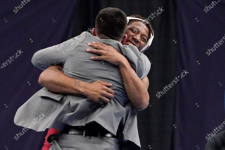 Iowa State's David Carr celebrates with coach Brent Metcalf, front, after defeating Rider's Jesse Dellavecchia during their 157-pound match in the finals of the NCAA wrestling championships, in St. Louis
