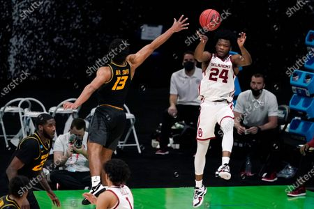 Oklahoma guard Elijah Harkless (24) passes over Missouri guard Mark Smith (13) during the second half of a first-round game in the NCAA men's college basketball tournament at Lucas Oil Stadium, in Indianapolis