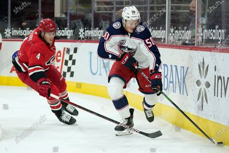 Carolina Hurricanes defenseman Haydn Fleury (4) chases Columbus Blue Jackets left wing Eric Robinson (50) during the first period of an NHL hockey game in Raleigh, N.C