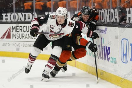 Arizona Coyotes' Jakob Chychrun, left, and Anaheim Ducks' Ryan Getzlaf chase the puck during the second period of an NHL hockey game, in Anaheim, Calif