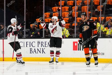 Arizona Coyotes' Derick Brassard, center, celebrates his hat trick with Tyler Pitlick, left, as Anaheim Ducks' Ryan Getzlaf skates past during the second period of an NHL hockey game, in Anaheim, Calif