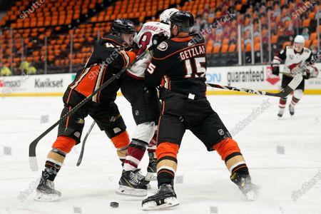 Arizona Coyotes' Nick Schmaltz, center, is shoved by Anaheim Ducks' Ryan Getzlaf, right, and Max Jones during the third period of an NHL hockey game, in Anaheim, Calif. The Coyotes won 5-1