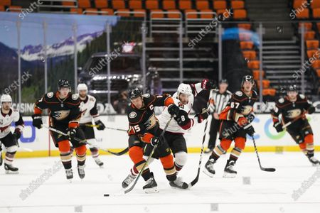 Anaheim Ducks' Ryan Getzlaf, center left, moves the puck past Arizona Coyotes' Nick Schmaltz during the third period of an NHL hockey game, in Anaheim, Calif