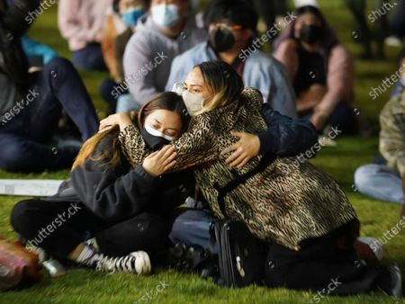 """Alanav Hillman, left, and Ashley Alexander hug as they join hundreds of people gathered at a rally """"Stop Asian Hate"""" candlelight vigil at Almansor Park in Alhambra, Calif., Saturday night, . Four days after six women of Asian descent were among the eight people killed in attacks on three Atlanta-area massage businesses. The """"LA vs. Hate"""" initiative encourages people to call 211 if they are victims or witness an incident of hate"""