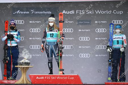 New Zealand's Alice Robinson, center, winner of an alpine ski, women's World Cup giant slalom, poses on the podium with second placed United States' Mikaela Shiffrin, left, and third placed Slovenia's Meta Hrovat, in Lenzerheide, Switzerland