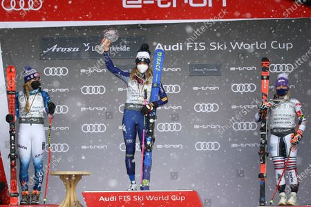 Italy's Marta Bassino, center, holds the trophy of the alpine ski, women's World Cup giant slalom discipline title, flanked by second placed United States' Mikaela Shiffrin, left, and third placed France's Tessa Worley in Lenzerheide, Switzerland