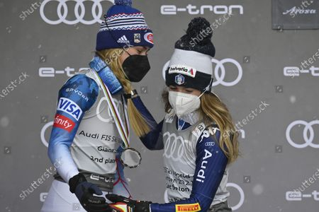 USA's second placed Mikaela Shiffrin (L) and Italy's first placed Marta Bassino celebrate on the podium during the award ceremony of the Women's overall Giant Slalom competition at the FIS Alpine Skiing World Cup finals in Lenzerheide, Switzerland, 21 March 2021.