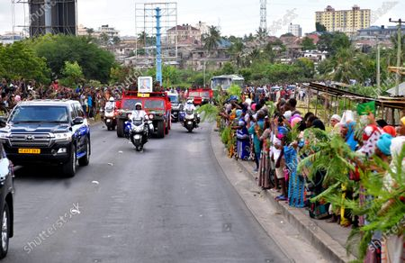 People line the street as a vehicle carrying former Tanzanian President John Magufuli's coffin passes through Dar es Salaam, Tanzania, March 20, 2021. Tanzanian President Samia Suluhu Hassan on Saturday led her fellow citizens in paying the last respects to former President John Magufuli at the Uhuru Stadium in Dar es Salaam. Magufuli, 61, died from a heart condition on Wednesday at the Emilio Mzena Hospital in the country's commercial capital.