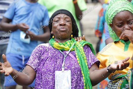 Two women cry when paying tribute to former Tanzanian President John Magufuli at Uhuru stadium in Dar es Salaam, Tanzania, March 20, 2021. Tanzanian President Samia Suluhu Hassan on Saturday led her fellow citizens in paying the last respects to former President John Magufuli at the Uhuru Stadium in Dar es Salaam. Magufuli, 61, died from a heart condition on Wednesday at the Emilio Mzena Hospital in the country's commercial capital.