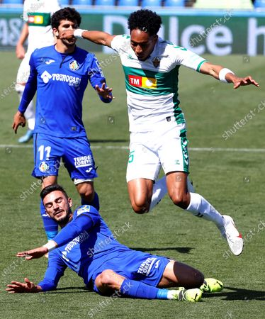 Elche's Johan Mojica (R) in action against Getafe's Carles Alena (bottom) during the Spanish La Liga soccer match between Getafe CF and Elche CF at Coliseum Alfonso Perez stadium in Getafe, near Madrid, Spain, 21 March 2021.
