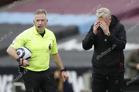 Referee Jon Moss (L) and West Ham manager David Moyes (R) react during the English Premier League soccer match between West Ham United and Arsenal FC in London, Britain, 21 March 2021.