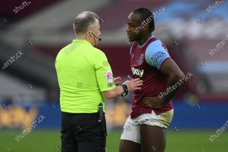 Referee Jon Moss (L) talks to West Ham's Michail Antonio (R) during the English Premier League soccer match between West Ham United and Arsenal FC in London, Britain, 21 March 2021.