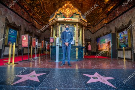"James Wood, general manager for The El Capitan Theatre, poses for a photo between movies. Movie-goers were spread out with COVID-19 safety precautions in effect, watch Disney's ""Raya and the Last Dragon"" during The El Capitan Theatre's reopening after some pandemic restrictions are lifted Friday, March 19, 2021 in Hollywood, CA. The theatre was limited to 100 guests and alternating rows of seats were blocked to create forward and rear spacing of 6 feet. Physically distanced queues and physical barriers. Face coverings are required and hand sanitizers are available for guest use. (Allen J. Schaben / Los Angeles Times)"
