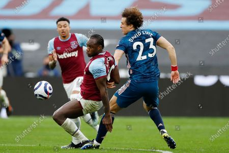 Stock Image of West Ham's Michail Antonio, left, challenges for the ball with Arsenal's David Luiz during the English Premier League soccer match between West Ham United and Arsenal at the London Stadium in London, England
