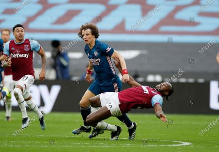 Stock Photo of West Ham's Michail Antonio, right, challenges for the ball with Arsenal's David Luiz during the English Premier League soccer match between West Ham United and Arsenal at the London Stadium in London, England