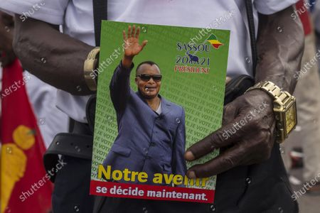 Stock Photo of A supporter of President Denis Sassou N'Guesso holds his photo during the last rally of the presidential campaign in Brazzaville, Congo. Republic of Congo pressed ahead Sunday March 21, 2021 with an election in which President Denis Sassou N'Guesso is widely expected to extend his 36 years in power, while the leading opposition candidate was flown to France after suffering COVID-19 complications