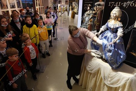 Stock Photo of Visitors look at an Empress of Russia Elizabeth Petrovna doll at an exhibition of Russian Monarchs porcelain dolls by Russian artist Olina Ventsel at the Doll Museum in the VDNH multifunctional exhibition center during the World Puppetry Day in Moscow, Russia, 21 March 2021. The exhibition of consists of over 50 dolls made by hand.