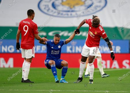 Manchester United's Anthony Martial, left, and Manchester United's Paul Pogba help Leicester's Youri Tielemans after he was injured during the English FA Cup quarter final soccer match between Leicester City and Manchester United at the King Power Stadium in Leicester, England