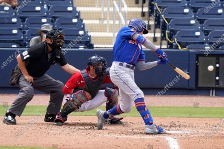New York Mets' Brandon Nimmo, right, singles during the fifth inning of a spring training baseball game against the Washington Nationals, in West Palm Beach, Fla