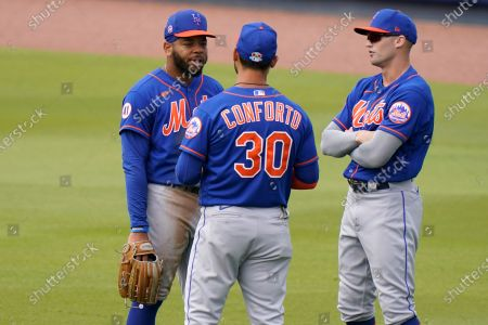 New York Mets left fielder Dominic Smith, left, right fielder Michael Conforto (30) and center fielder Brandon Nimmo, right, talk during a pitching change during the fifth inning of a spring training baseball game, in West Palm Beach, Fla