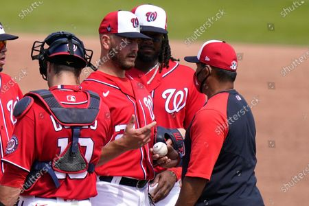 Washington Nationals relief pitcher Tanner Rainey, left, talks with manager Dave Martinez, right, as he is relieved during the sixth inning of a spring training baseball game against the New York Mets, in West Palm Beach, Fla