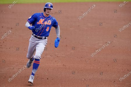 New York Mets' Brandon Nimmo (9) runs to third base on a double hit by Dominic Smith during the first inning of a spring training baseball game against the Washington Nationals, in West Palm Beach, Fla