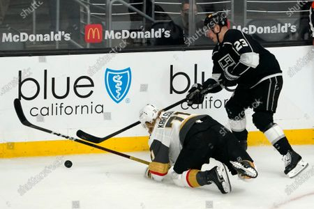 Vegas Golden Knights center William Karlsson, left, falls while under pressure from Los Angeles Kings right wing Dustin Brown during the first period of an NHL hockey game, in Los Angeles