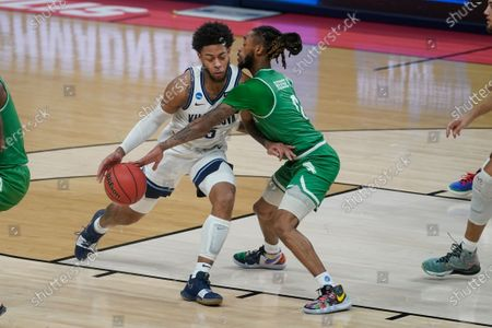 Stock Image of Villanova's Justin Moore (5) is defended by North Texas' James Reese (0) during the first half of a second-round game in the NCAA men's college basketball tournament at Bankers Life Fieldhouse, in Indianapolis