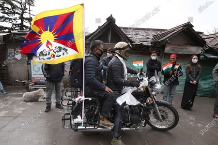 Stock Image of Tibetan youth Tsering Yeshi (R) rides his bike at the beginning of a campaign for conferring the Bharat Ratna, Indian highest civilian award, on Tibetan spiritual leader the Dalai Lama, at McLeod Ganj, near Dharamsala, India, 22 March 2021. Yeshi started a campaign on his bike and is expected to drive throughout the country on a campaign for the conferment of the award on the Dalai Lama.