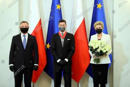 Bayern Munich's Polish striker Robert Lewandowski (C) is flanked by Polish President Andrzej Duda (L) and First Lady Agata Kornhauser-Duda (R) during the award ceremony of the Commander's Cross of the Order of Polonia Restituta at the Presidential Palace in Warsaw, Poland, 22 March 2021. Polish national soccer team captain Robert Lewandowski was appreciated for his outstanding sports achievements and promoting Poland on the international stage.