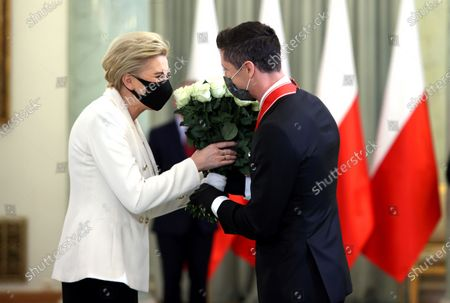 Bayern Munich's Polish striker Robert Lewandowski (R) receives flowers from Polish First Lady Agata Kornhauser-Duda (L) during the award ceremony of the Commander's Cross of the Order of Polonia Restituta at the Presidential Palace in Warsaw, Poland, 22 March 2021. Polish national soccer team captain Robert Lewandowski was appreciated for his outstanding sports achievements and promoting Poland on the international stage.