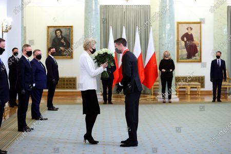 Bayern Munich's Polish striker Robert Lewandowski (C-R) receives flowers from Polish First Lady Agata Kornhauser-Duda (C-L) during the award ceremony of the Commander's Cross of the Order of Polonia Restituta at the Presidential Palace in Warsaw, Poland, 22 March 2021. Polish national soccer team captain Robert Lewandowski was appreciated for his outstanding sports achievements and promoting Poland on the international stage.