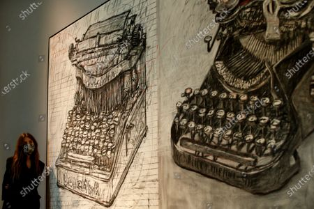A member of staff poses with 'Large Typewriters', by South African artist William Kentridge, estimated at GBP350,000-550,000,