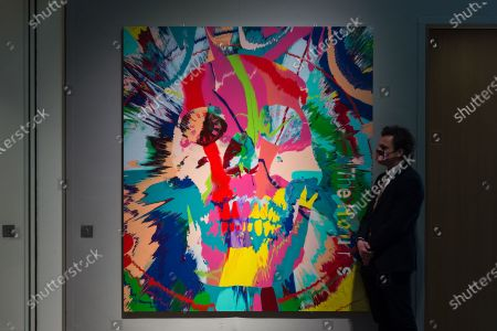 A staff member looks at painting by Damien Hirst (b. 1965) Beautiful Hours Spin Painting IX (2008), estimate: £150,000 - 200,000 during a photo call for Bonhams' 20/21 Century Week - a series of auctions celebrating the last one hundred years in art, on March 22, 2021 in London, England.