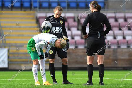Alice Carlsson (#20 Hammarby) is hurt and watched by Anna Tamminen (#1 Hammarby) and referee Lovisa Johansson