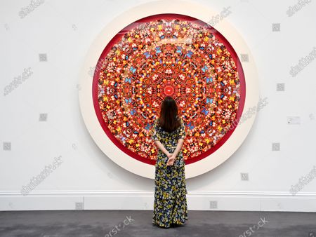 A Sotheby's employee poses for photographers next to the art piece 'The Human Voice' by British artist Damien Hirst at Sotheby's, London,  Britain, 22 March 2021. The Modern Renaissance sale is expected to be the auction house's first major sale of 2021.
