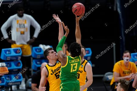 Oregon forward Chandler Lawson (13) shoots on Iowa center Luka Garza (55) during the first half of a men's college basketball game in the second round of the NCAA tournament at Bankers Life Fieldhouse in Indianapolis
